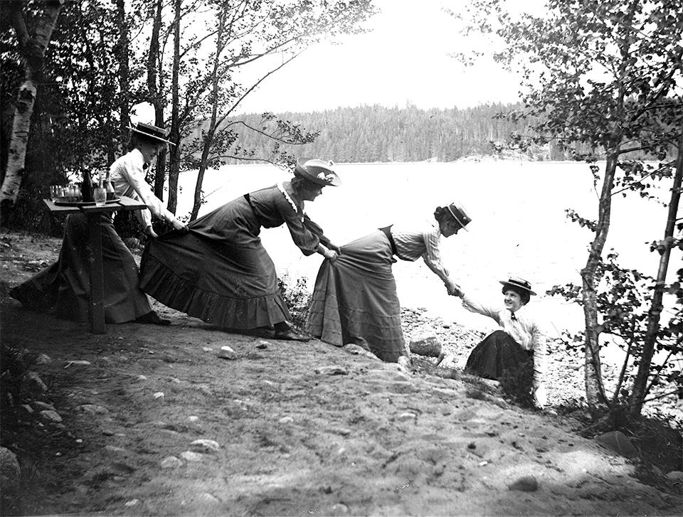 Tre kvinnor i rad som drar upp en kvinna ur sjön