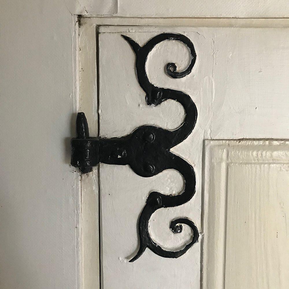 Gammal vitmålad dörr med beslag i svart.