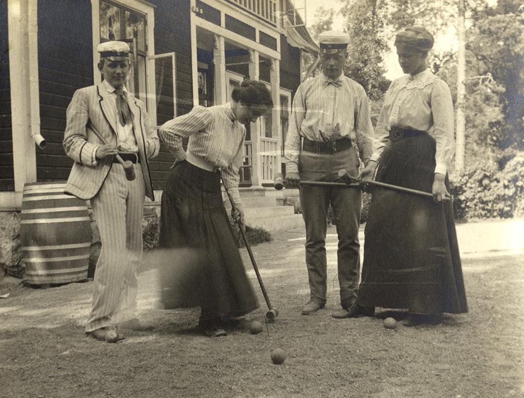 Två män och två kvinnor framför ett hus.