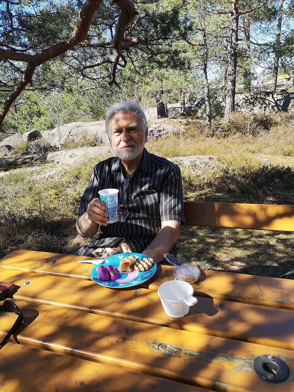 Man som sitter i skuggan vid ett bord och dricker kaffe.